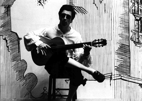 Wolfgang Gerhard mit Gitarre vor gemaltem Hintergrund (Sizilien).